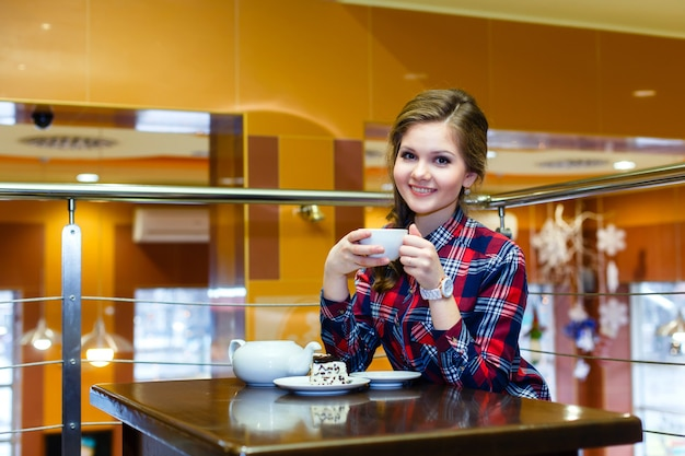 Smiling beautiful girl in a plaid shirt drinking tea in a cafe