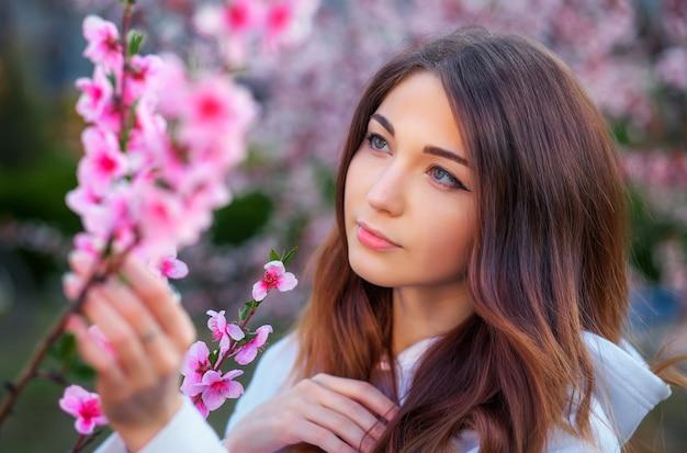 日没時に桃の木の近くに立っている美しい少女の笑顔。笑顔。春の時間。