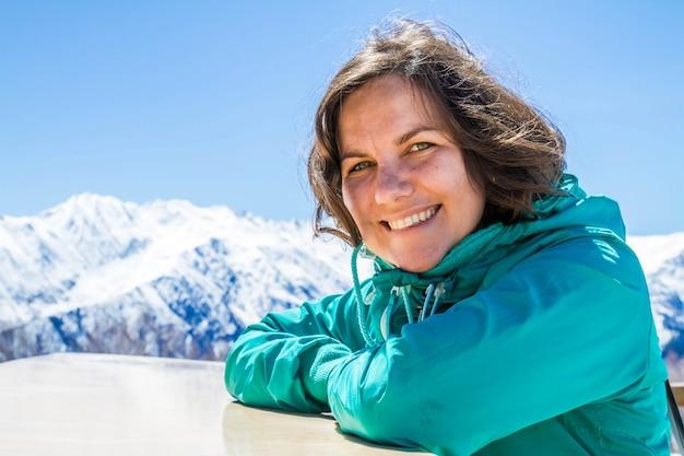 Улыбающаяся красивая девушка остается под панорамой гор грузии ужба и леденцом в снежной шапке