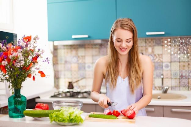 明るいモダンなターコイズ料理の背景にサラダスライストマトとキュウリのブロンドの髪を持つ美しい少女の笑顔