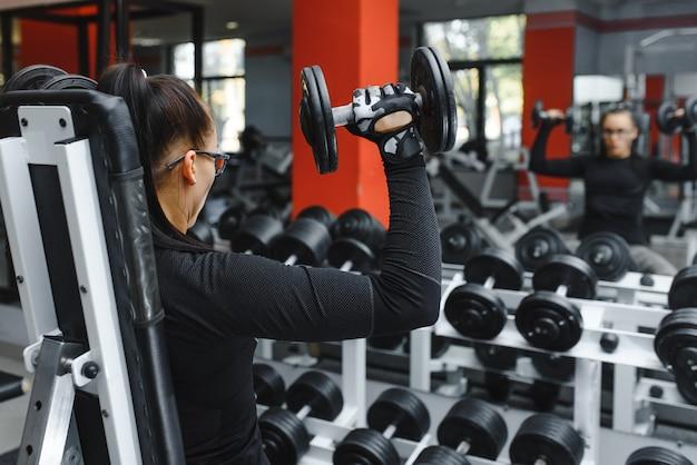 Улыбающаяся красивая девушка с тяжелыми гантелями перед зеркалом в спортивном зале. сильная молодая красивая женщина занимается в тренажерном зале с гантелями перед зеркалом.