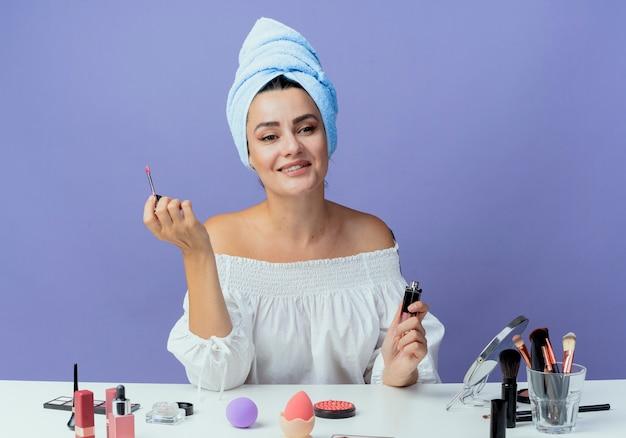 Улыбающаяся красивая девушка, завернутая в полотенце для волос, сидит за столом с инструментами для макияжа, держа блеск для губ, глядя в сторону, изолированную на фиолетовой стене