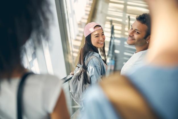 다른 나라로 비행기로 여행하기 위해 국제 공항의 게이트로 이동하는 동안 분홍색 모자에 아름다운 인도 젊은 아가씨가 행복해집니다.