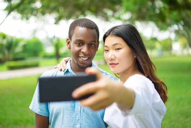 Smiling beautiful interracial couple taking selfie in summer park.