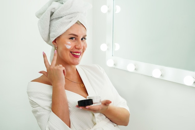 Smiling beautiful lady apply skincare cream on face look in bathroom mirror happy young woman wrap t...