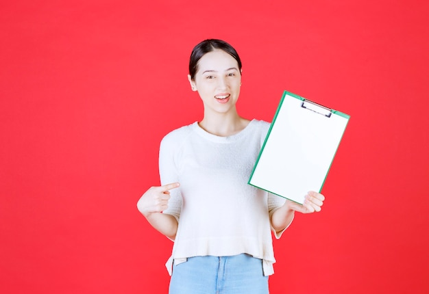Smiling beautiful lady holding clipboard and points finger on it