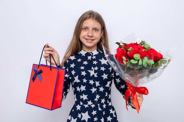 Smiling beautiful little girl on happy women's day holding out bouquet with gift bag at camera isolated on white wall