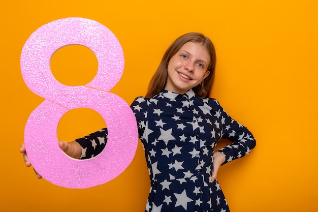 Smiling beautiful little girl on happy women's day holding out number eight at camera isolated on orange wall