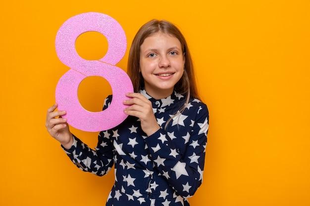 8番を保持している幸せな女性の日に美しい少女の笑顔