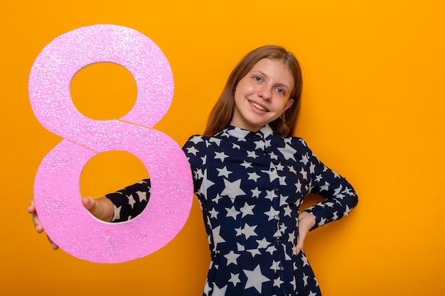Улыбающаяся красивая маленькая девочка в счастливый женский день, протягивая номер восемь перед камерой, изолированной на оранжевой стене