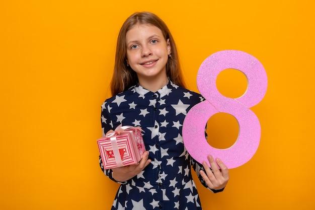 プレゼントで8番を差し出して幸せな女性の日に美しい少女の笑顔
