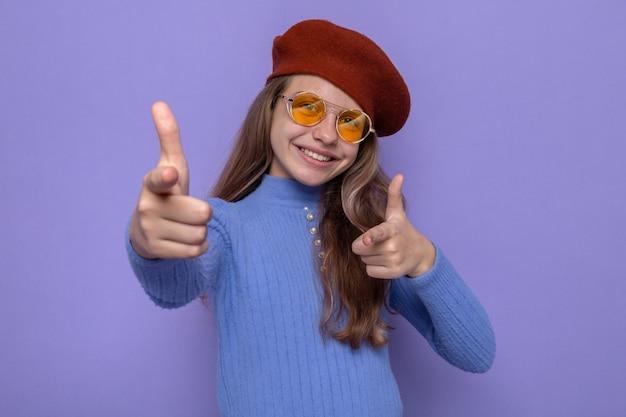 Sorridente bella bambina che punta davanti, indossando un cappello con gli occhiali
