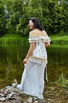 コルセットとペチコートを着た笑顔の美しい成熟した女性は、野生の川岸に沿って歩いています。