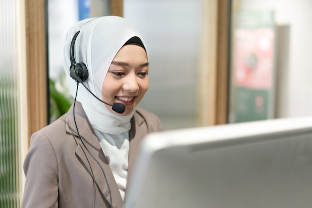 Smiling beautiful muslim woman working care customer service wearing headphone talking with customer at office