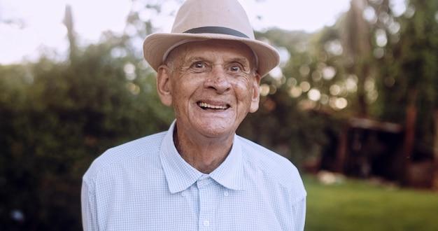 Smiling beautiful older male latin farmer elderly man at farm in summer day