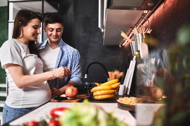 웃는 아름 다운 임신 한 여자와 남자는 부엌에서 커피를 마시고 요리. 새로운 삶, 임신을 기다리고 있습니다.