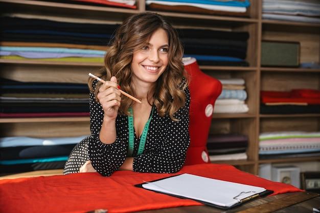Улыбающаяся женщина красивая швея работает в мастерской, рисует эскиз