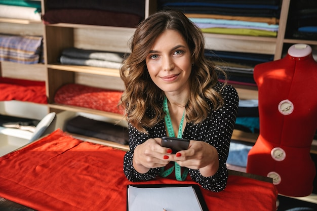 Улыбающаяся женщина красивая швея работает в мастерской, используя мобильный телефон