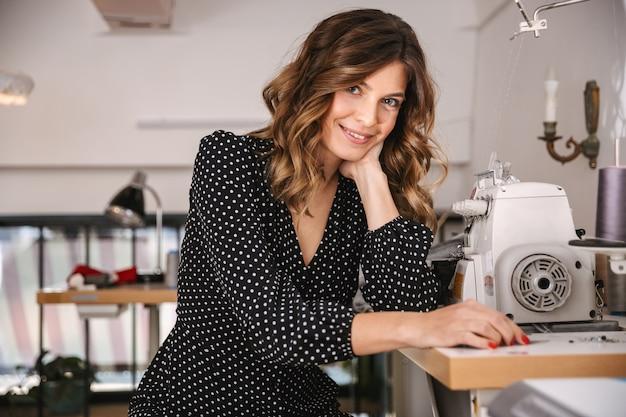 Улыбающаяся женщина красивая швея работает в мастерской, используя швейную машину