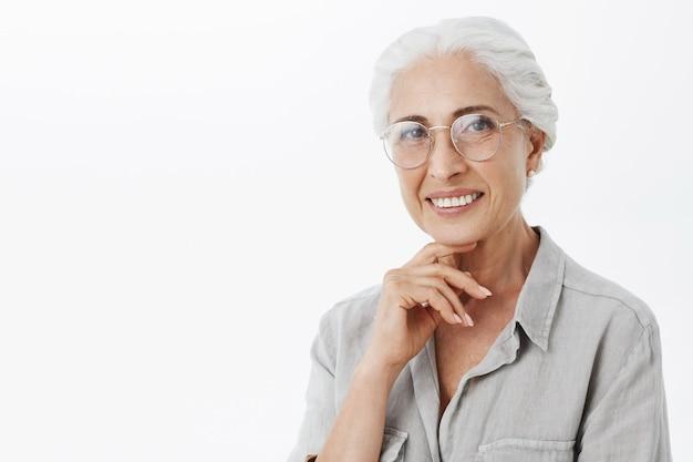 Bella donna senior sorridente in vetri che sembrano contenti