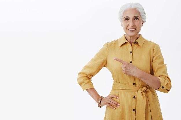 Улыбается красивая старшая женщина в желтом пальто, указывая пальцем влево, показывая рекламу