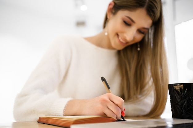 Smiling beautiful student female with long hair in white sweater writing in notebook while using the laptop. remote studing