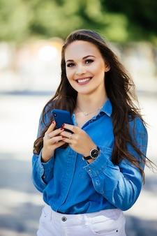 通りでスマートフォンを使用して美しい都会の女性の笑顔