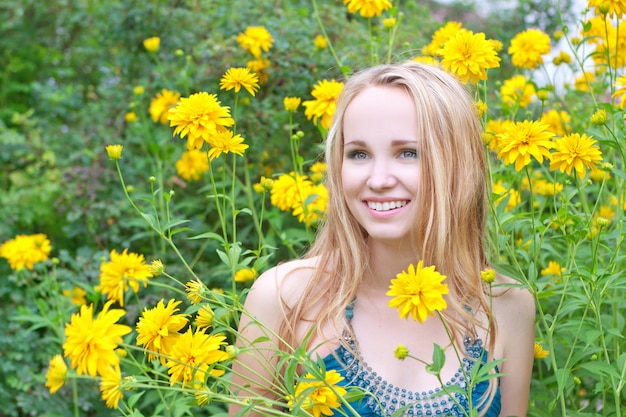 Smiling beautiful woman among  flowers