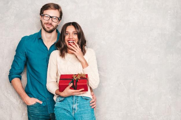 웃는 아름다운 여자와 그녀의 잘생긴 남자친구. 회색 벽 근처에서 포즈를 취하는 행복한 쾌활한 가족. 발렌타인 데이. 모델들이 여자친구에게 선물 상자를 껴안고 주고 있습니다.
