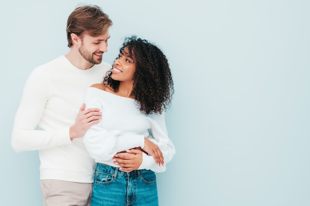 笑顔の美しい女性と彼女のハンサムな彼氏。灰色の優しい瞬間を持っている幸せな陽気な多民族家族