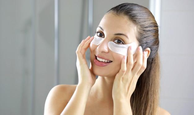 Улыбается красивая женщина, применяя маску под глазами против усталости, глядя в зеркало в ванной комнате.