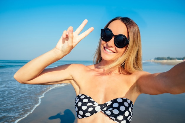 Smiling and beautiful woman doing selfie on vacation.