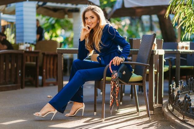 Улыбающаяся красивая женщина, одетая в элегантный синий костюм, сидит в кафе в солнечный день