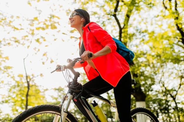 Acqua potabile della bella donna sorridente in bottiglia che fa sport nella mattina nel parco