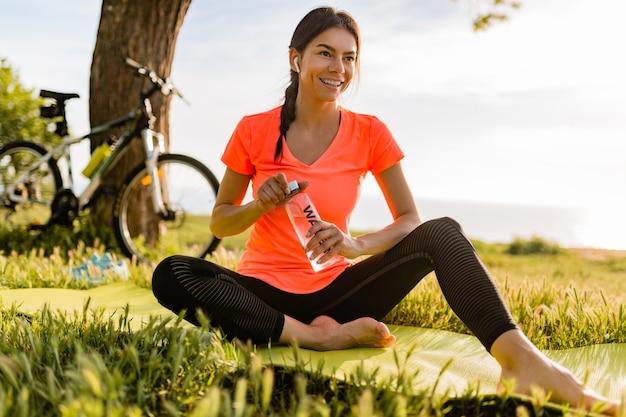 公園で朝のスポーツをしているボトルの水を飲む美しい女性の笑顔