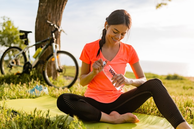 Улыбается красивая женщина с питьевой водой в бутылке, занимаясь спортом утром в парке