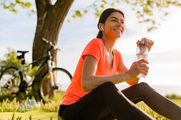 공원에서 아침에 스포츠를하는 병에 웃는 아름다운 여자 식수