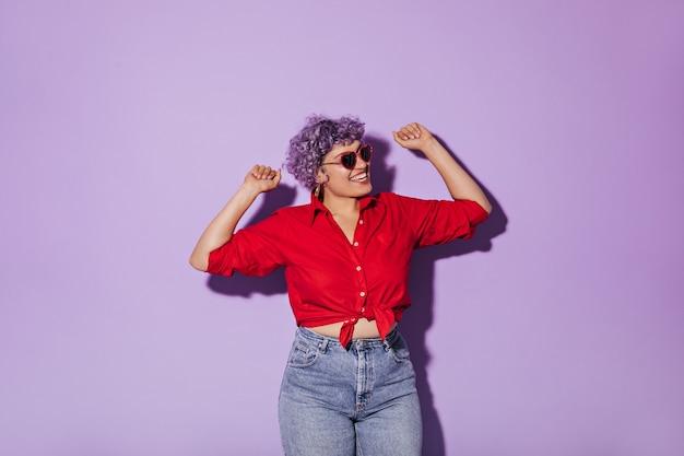 La bella donna sorridente in occhiali da sole a forma di cuore in camicia rossa si rallegra del lillà isolato. donna in pose di jeans