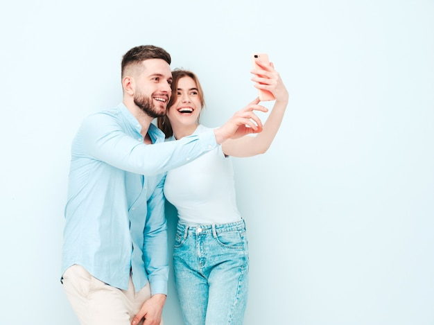 Smiling beautiful woman and her handsome boyfriend. happy cheerful family having tender moments near light blue wall in studio