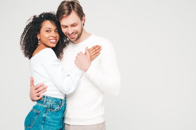 Smiling beautiful woman and her handsome boyfriend. happy cheerful multiracial family having tender moments on grey