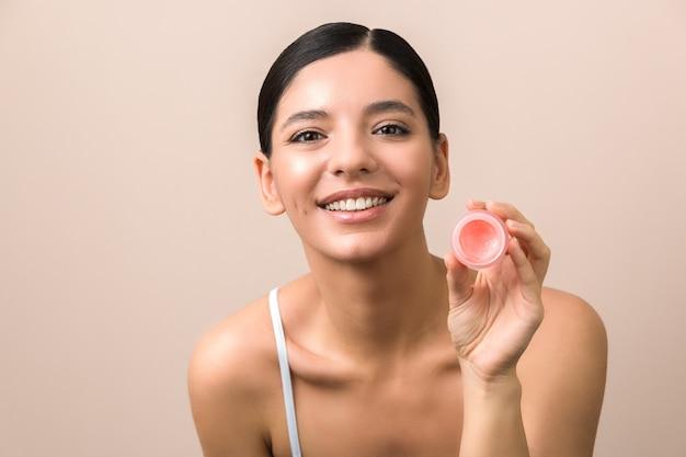 Smiling beautiful woman holding lip balm