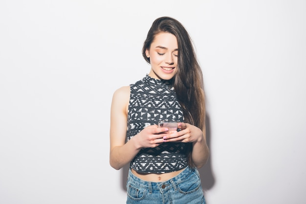 Smiling beautiful woman holding mobile phone isolated on a white wall