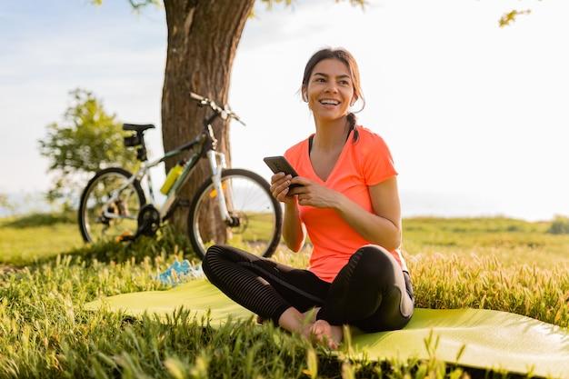 Улыбающаяся красивая женщина, держащая телефон, занимается спортом утром в парке природы
