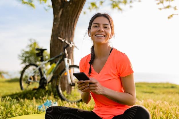 Улыбающаяся красивая женщина, держащая телефон, занимается спортом утром в парке