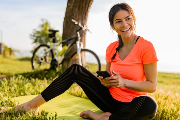 公園で朝のスポーツをしている電話を持っている美しい女性