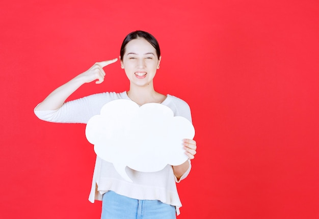 Smiling beautiful woman holding speech bubble with a cloud shape