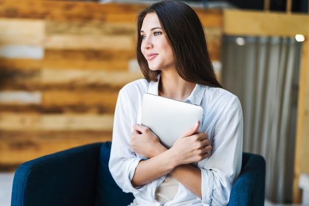 白いシャツを着た笑顔の美しい女性は、肘掛け椅子に座って、スマートタブレットをしっかりと握り締めます。