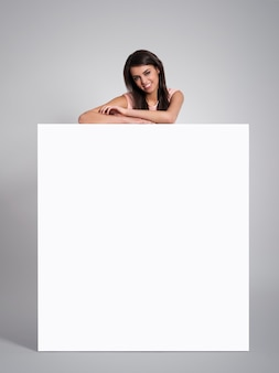 Smiling beautiful woman leaning on empty whiteboard