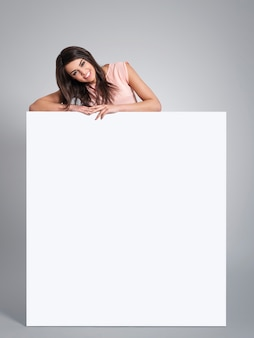 Smiling beautiful woman leaning on empty whiteboard
