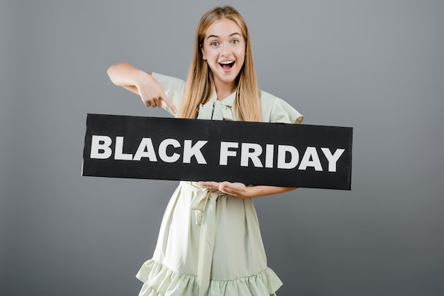 Smiling beautiful woman pointing finger at black friday sign isolated over grey